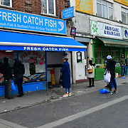 A Security Man During the coronavirus in UK lockdown people out shopping queue at the front of a fish shop,on 28 March 2020, at Walthamstow Market, London.