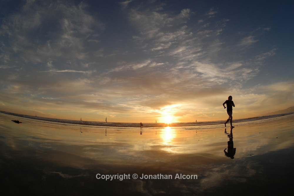A girl runs on the wet sand as the sun sets on another warm winter day at the beach on January 18, 2015 in Venice, California