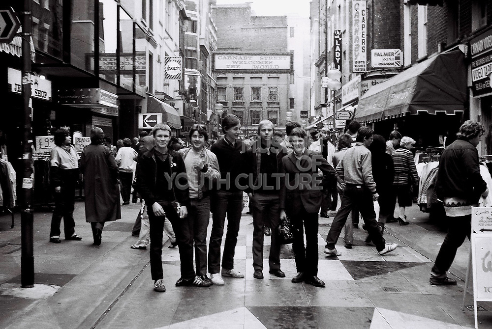 A group of five friends stand in Carnaby street in front of the Carnaby street welcome sign. London, Carnaby street, UK, 1980s.
