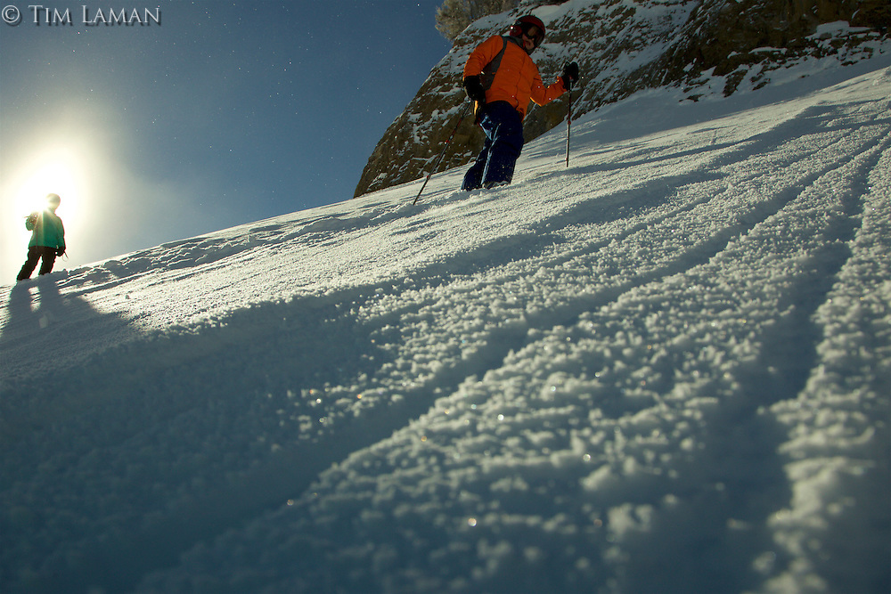 Russell Laman (age 12) and Jessica Laman (age 9) hike up a slope below cliffs to get first tracks in fresh powder snow in Jackson Hole, Wyoming