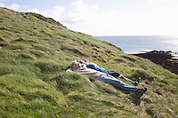 Mature couple lie with hands behind head in coastal landscape