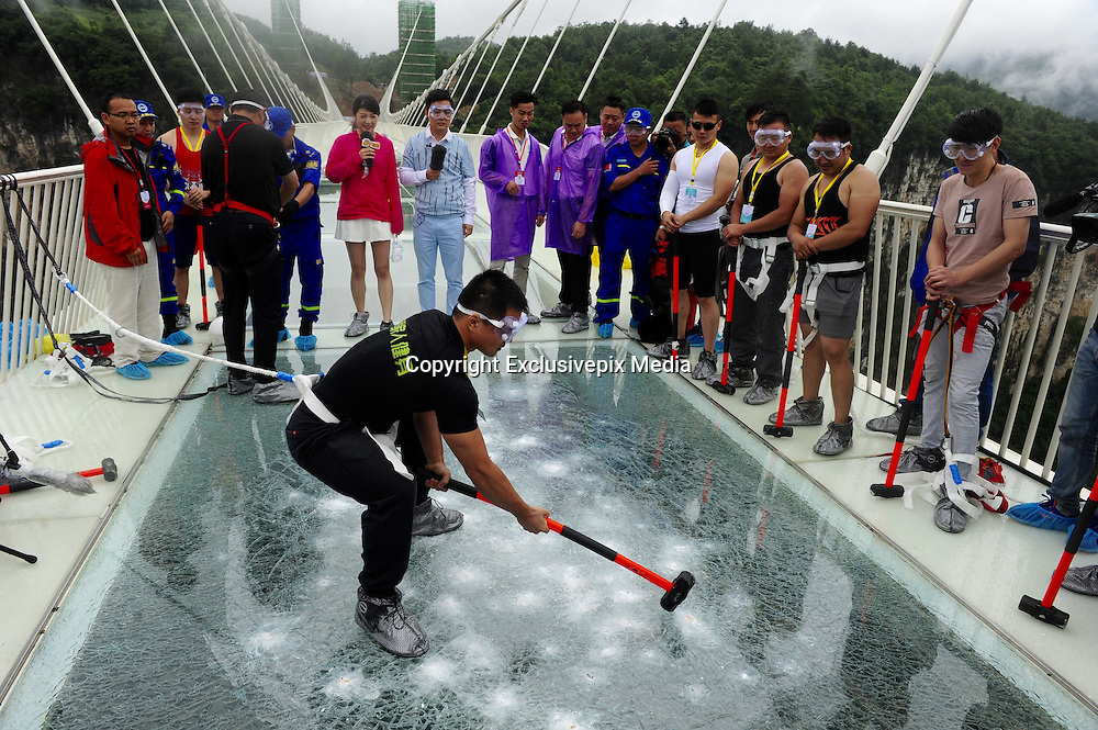 ZHANGJIAJIE, CHINA - JUNE 25:<br /> <br />  A visitor strikes the glass-bottomed bridge with a hammer for a safety test at Zhangjiajie Grand Canyon on June 25, 2016 in Zhangjiajie, Hunan Province of China. World\'s tallest and longest glass-bottomed bridge has been completed and took a global broadcast through television and internet medias to show its safety. More than thirty citizens and visitors thumped the bridge with hammer in the test event. <br /> ©Exclusivepix Media