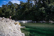 A woman admires the clear water of the Pelorus River in the Marlborough region of New Zealand