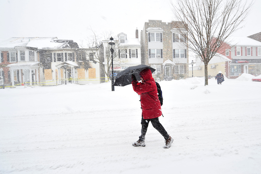 A woman with an umbrella walks through deep snow and blizzard conditions on Broad Street Thursday, Feb. 13, 2014 in Bethlehem, PA. (AP Photo/Chris Post)