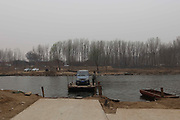 BEIJING, CHINA - <br /><br />Ferrying Office Workers And Their Cars on wooden boat <br /><br />A man sitting in his car takes a wooden boat to cross the Chaobai River in Beijing, China. Some office workers who live in Hebei will drive cars to the Chaobai River, and then let a boat take them with their cars to the bank in Beijing during rush hours every day.<br />©Exclusivepix Media