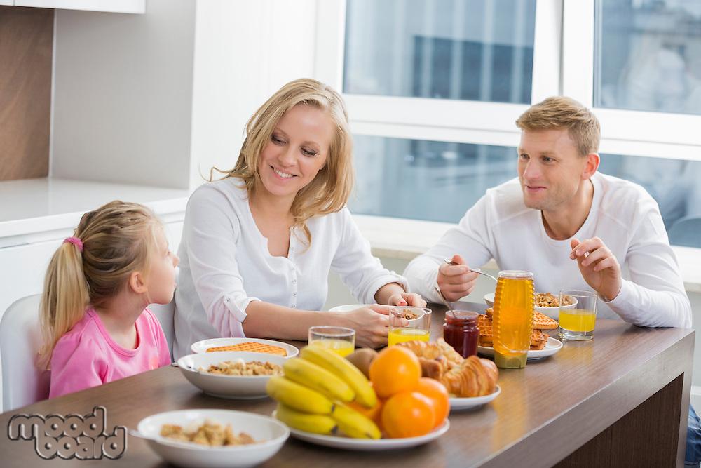 Happy family of three having breakfast at table