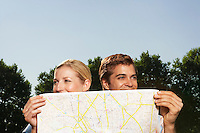 Lost smiling young couple in park holding map