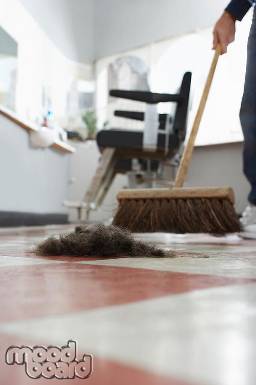 Barber sweeping floor in barber shop
