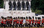 Marching grenadier bandsmen pass the war memorial in Horseguards Parade on the Queen's official Trooping the Colour ceremony