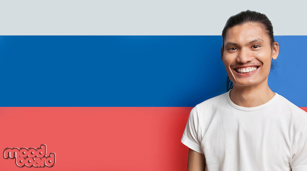 Portrait of happy young mixed race man standing against French flag