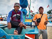 18 JULY 2016 - KUTA, BALI, INDONESIA:  Crewmen wait to board their small fishing canoe in the fish market at Pasar Ikan pantai Kedonganan.   PHOTO BY JACK KURTZ