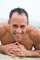 Shirtless wet man leaning on the edge of a wooden dock smiling