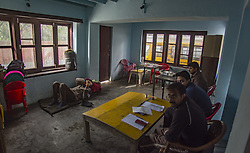 October 10, 2018 - Srinagar, Jammu and Kashmir, India - Kashmiri polling officials wait for people to cast their vote in a deserted polling station, during the second phase of municipal polls, in Srinagar, the summer capital of Indian administered Kashmir, India. Poor voter turnout marked the second phase of municipal elections in Kashmir amid a partial shutdown and heavy deployment of government forces across the region. Pro-independence groups have rejected the polls as farce and  called for a boycott while major pro-India parties like National Conference and Peoples Democratic Party (PDP) also stayed away from the electoral process alleging Indian government's attempts to alter the special status accorded to the disputed Himalayan region in the country's Constitution. (Credit Image: © Yawar Nazir/ZUMA Wire)