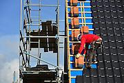 Nederland, Nijmegen, 27-2-2014Bouwplaats voor huizen in de nieuwe wijk Laauwik, onderdeel van de stadsuitbreiding Waalsprong van Nijmegen in Lent.Er worden hier veel verschillende woningtypen gebouwd, zowel voor sociale huur,koop en vrije sector. Dakdekker, bouwvakker, bezig met het leggen van pannen op een dak.Opleiding, scholing,.vakman, ambacht,vak,Foto: Flip Franssen/Hollandse Hoogte