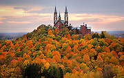 Holy Hill is shown Monday among a bed of fall colored trees near dusk. JEFFREY PHELPS PHOTO.