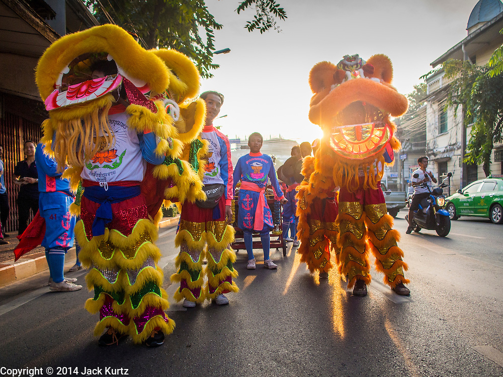 30 OCTOBER 2014 - BANGKOK, THAILAND: Chinese lion dancers perform at sunrise on Bamrung Muang Street during the parade marking the start of the annual temple fair at Wat Saket. Wat Saket is on a man-made hill in the historic section of Bangkok. The temple has golden spire that is 260 feet high which was the highest point in Bangkok for more than 100 years. The temple construction began in the 1800s in the reign of King Rama III and was completed in the reign of King Rama IV. The annual temple fair is held on the 12th lunar month, for nine days around the November full moon. During the fair a red cloth (reminiscent of a monk's robe) is placed around the Golden Mount while the temple grounds hosts Thai traditional theatre, food stalls and traditional shows.   PHOTO BY JACK KURTZ