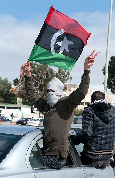 A masked man shows his support for the Opposition as he rides in a car through Benghazi.