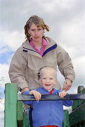 Single mother standing at top of slide in playground with young son,