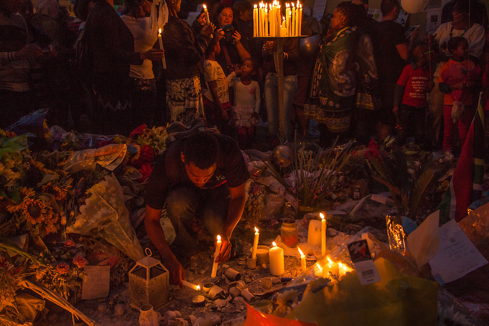 A young man lights a candle in memory of Nelson Mandela outside his Johannesburg house in Houghton on Saturday Dec.7 2013.