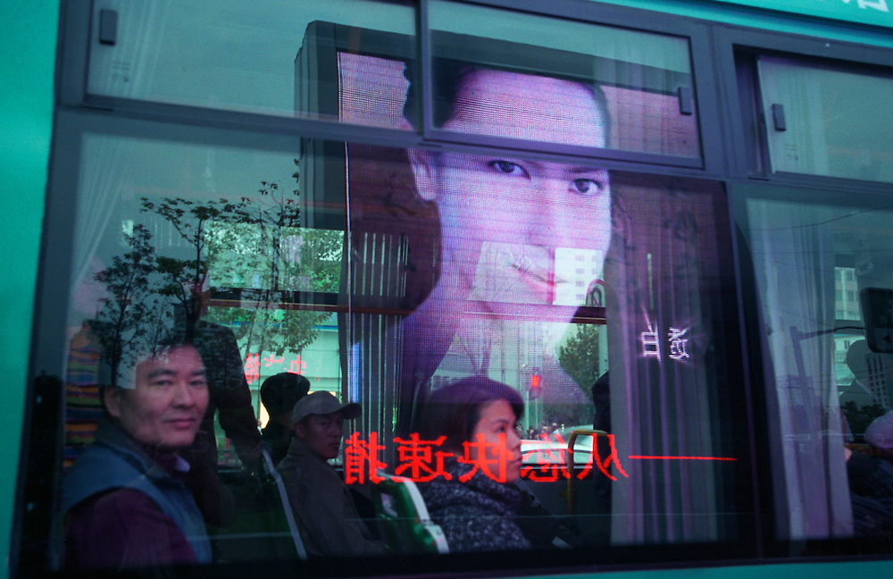 Large screen advertising monitors reflected in a city bus on Nanjing Donglu, Shanghai's shopping street. As China's economy continues to boom, more and more chinese are obtaining the modern, energy consuming amenities that wealth and improved living standards bring. China's soaring demand for energy is having serious effects on the environment. 75% of China's energy needs is supplied by coal, the cheapest and dirtiest form of energy, and seven of the world's ten most polluted cities are in China...Shanghai, China. 19/11/2005..Photo © J.B. Russell