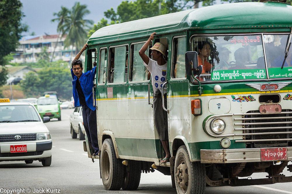 19 JUNE 2013 - YANGON, MYANMAR: Conductors lean out the doors of a Yangon bus. Yangon buses are generally overcrowded and in poor repair but as the economy improves newer, but still used, Japanese and Korean buses are being imported. Hundreds of bus routes criss-cross Yangon, providing the cheapest way of getting around the city. Most fares are less than the equivalent of .20¢ US.   PHOTO BY JACK KURTZ