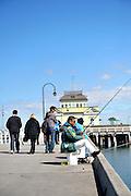 Fishermen on  the St Kilda pier, with pavillion kiosk in background. St Kilda, Melbourne, Australia