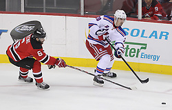 May 19, 2012; Newark, NJ, USA; New York Rangers left wing Chris Kreider (20) makes a pass while being defended by New Jersey Devils defenseman Andy Greene (6) during the second period in game three of the 2012 Eastern Conference Finals at the Prudential Center.