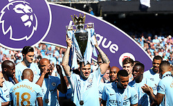 Manchester City goalkeeper Ederson celebrates with the trophy and team-mates