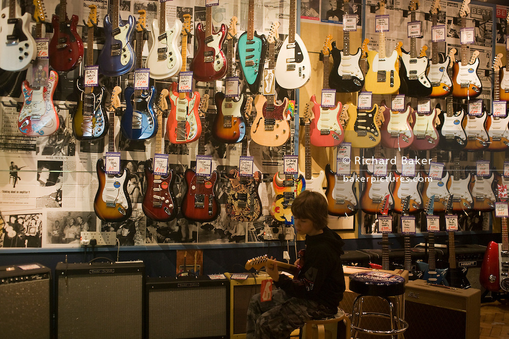 A 10 year-old boy plays an amplified electric Fender Stratocaster guitar at Regent Sound at 4 Denmark Street, Tin Pan Alley