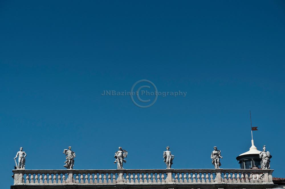 The six divinities (Hercules,  Jupiter, Venus, Mercury, Apollo and Minerva)atop the Palazzo Maffei in Verona, Italy.
