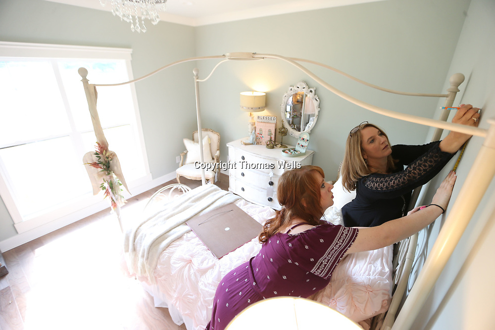 Amber Beane, left, and Shelly Coggins hang a piece of art over the childrens bed in the St. Jude Dream Home on ROwan Oak in Tupelo.