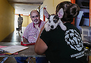 A man registers his dog at a low cost spay and neuter clinic in Yabucoa, Puerto Rico, May 5, 2016. The clinic is a joint venture of The Sato Project and Humane Society International.