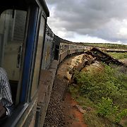 "Alloyce Ojiambo, the co-driver of the train from Nairobi to Mombasa, looks at a derailed train along the tracks. Also known as the ""Lunatic Express"", It was the railway line that built Kenya, linking the port town of Mombasa through the capital, Nairobi, to the shores of Lake Victoria and on to the Ugandan capital, Kampala. It cost $5m (in 1894 money) and countless workers died during its construction. There were derailments, collisions, tribal raids and attacks by lions. Yet despite becoming one of Kenya's national treasures and a vital economic artery for east Africa, the railway now lies in a state of disrepair. A South African consortium has taken it over and plans to invest millions, returning it to its former glory. But there has been a row over the railway's financing which may yet derail the .project. .."