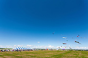 Kites soar high above the crowds and the tents at Windscape Kite Festival, Swift Current, Saskatchewan.
