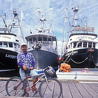 Canada, British Columbia, Prince Rupert, Bicyclist on dock at harbor on summer afternoon