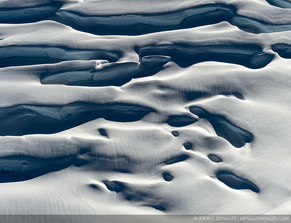 Deep crevasses of Margerie Glacier take on an other worldly look in early evening light in this photo taken at the uppermost region of the glacier just inside the U.S. at the Canadian border. The 21-mile-long glacier in Glacier Bay National Park and Preserve is one of the park&rsquo;s tidewater glaciers. <br /> <br /> Glacier Bay National Park is located in southeast Alaska. Known for its spectacular tidewater glaciers, icefields, and tall costal mountains, the park is also an important marine wilderness area. The park a popular destination for cruise ships, is also known for its sea kayaking and wildlife viewing opportunities. <br /> <br /> Glacier Bay National Park is home to humpback whales which feed in the park's protected waters during the summer, both black and grizzly bears, moose, wolves, sea otters, harbor seals, steller's sea lions and numerous species of sea birds. <br /> <br /> The dynamically changing park, known for its large, contiguous, intact ecosystems, is a United Nations biosphere reserve and a UNESCO World Heritage site.