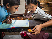 03 AUGUST 2015 - KATHMANDU, NEPAL:  A boy and girl study in a temporary school in central Kathmandu. Parts of her existing school were damaged in the earthquake and officials are afraid to use the existing structure, so they have set up a temporary school made of woven matting. The Nepal Earthquake on April 25, 2015, (also known as the Gorkha earthquake) killed more than 9,000 people and injured more than 23,000. It had a magnitude of 7.8. The epicenter was east of the district of Lamjung, and its hypocenter was at a depth of approximately 15 km (9.3 mi). It was the worst natural disaster to strike Nepal since the 1934 Nepal–Bihar earthquake. The earthquake triggered an avalanche on Mount Everest, killing at least 19. The earthquake also set off an avalanche in the Langtang valley, where 250 people were reported missing. Hundreds of thousands of people were made homeless with entire villages flattened across many districts of the country. Centuries-old buildings were destroyed at UNESCO World Heritage sites in the Kathmandu Valley, including some at the Kathmandu Durbar Square, the Patan Durbar Squar, the Bhaktapur Durbar Square, the Changu Narayan Temple and the Swayambhunath Stupa. Geophysicists and other experts had warned for decades that Nepal was vulnerable to a deadly earthquake, particularly because of its geology, urbanization, and architecture.    PHOTO BY JACK KURTZ