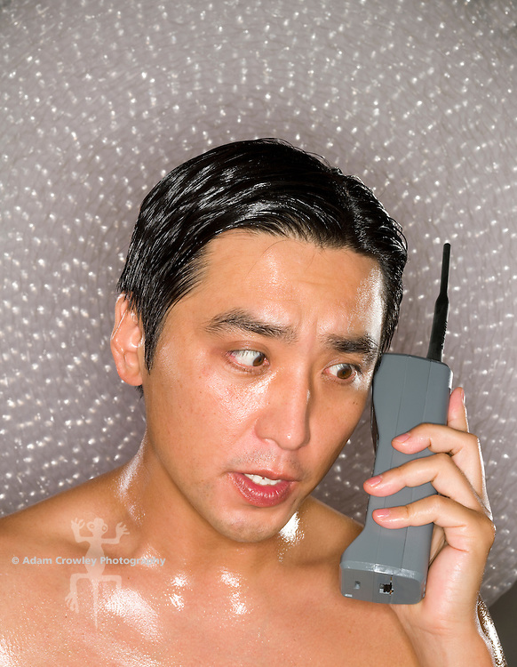 Headshot of a shirtless asian male (40-50 years old) talking on a vintage mobile phone.