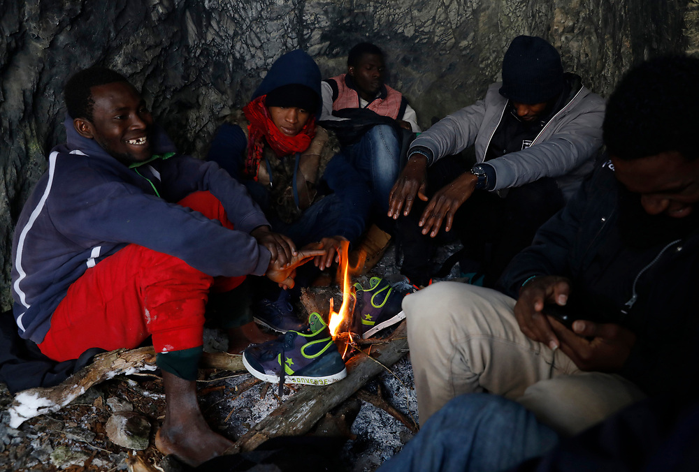 Migrants rest and warm up by a fire in a cave after crossing a part of the mountain range of the Alps from Italy into France, near the town of Nevache in southeastern France.