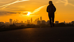 Primrose Hill, London, October 28th 2016. A jogger on Primrose Hill is thrown into silhouette against the city's skyscrapers as the sun rises over London.