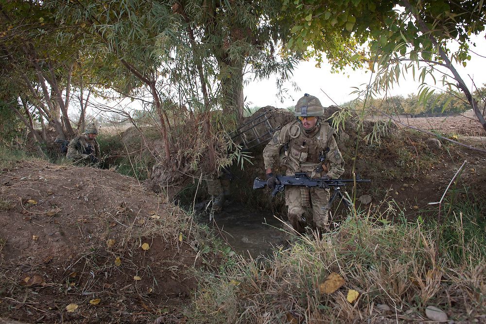 Lance Cpl 'Boycie' armed with a GPMG (General Purpose Machine Gun) plays a dangerous day long game of cat and mouse with insurgent gunmen as British soldiers from 1PWRR (Princess of Wales Regiment) are involved in an ongoing series of Operations called Tora Pishaw aimed at disrupting insurgent activity in their AO (Area of Operations). During the most recent 4 day operation the soldiers regularly came under fire from insurgents using small arms, belt fed machine guns and UGL's (Under Slung Grenade Launchers). The soldiers returned fire using shallow trenches on the edges of ploughed fields or irrigation ditches as cover. Nad I Ali North, Helmand Province, Afghanistan on the 13th of November 2011.