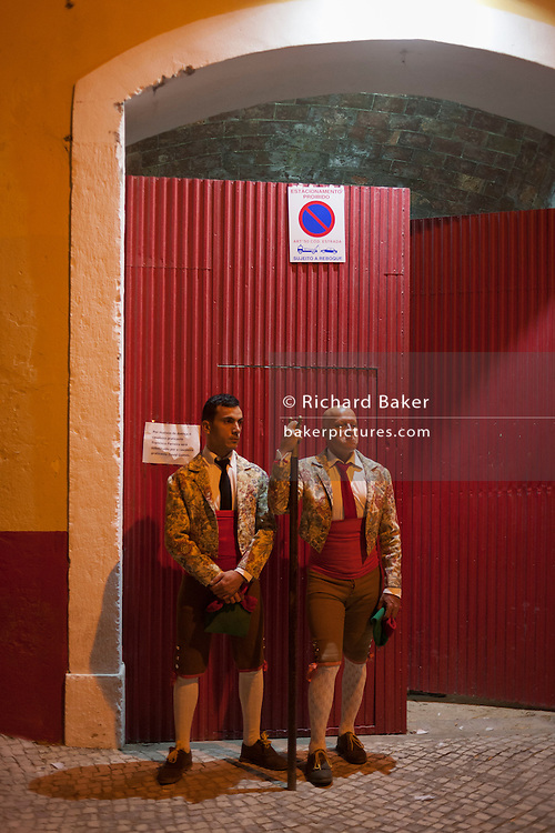 "Two Portugese Forcados stand outside the bullring before the evening's bullfight (Corrida de Touros), on 15th July 2016, at Caldas da Rainha, Portugal. A forcado is a member of a group of men that performs the pega de cara or pega de caras (""face catch""), the final event in a typical Portuguese bullfight. They were initially professionals from lower classes but nowadays people from all social backgrounds practice their art through amateur groups. In the Portuguese version, unlike Spanish bullfights, the bull is not killed. (Photo by Richard Baker / In Pictures via Getty Images)"