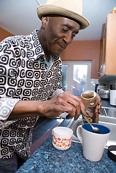 Older man at home in his kitchen making a hot drink,