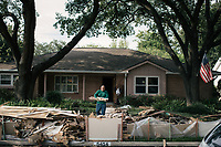 Amauri Alfonso cleans out the home of Dave Roseland after Harvey passed over the Meyerland area of Houston.