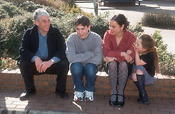 Family group sitting together on wall in sunshine,