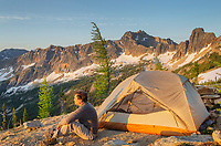 Adult male at daybreak sitting next to backpacking tent and gazing at view on ridge above Cutthroat Pass, near Pacific Crest trail. North Cascades Washington