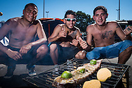 Martin, Maxi and Diego from Mendosa, Argentina, pose in front of a cooking fire with a large steak sizzling on top.They are living in a tent at the site set up for football fans who had nowhere to stay but the tents, campervans, cars and caravans that they had bought with them. The site, at the Terreirao Do Samba, Rio de Janeiro, Brazil, was arranged by the city government once they realised the number of fans in this situation was significant and rather than having them scattered about the sity they offered secure, enclosed accommodation with sanitation and water. The majority of fans at the site were Argentinian but there were also people from Chile, USA, Uruguay and Colombia. <br /> Picture by Andrew Tobin/Focus Images Ltd +44 7710 761829<br /> 06/07/2014