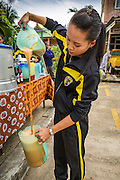 07 JULY 2013 - NARATHIWAT, NARATHIWAT, THAILAND:  A Thai Army Ranger makes iced Thai milk tea during a civilian outreach her unit held with Thai Marines in Narathiwat. Royal Thai Marines in Narathiwat province held a special ceremony Sunday in advance of Ramadan. They presented widows, orphans and indigent people with extra rice and food as a part of the Thai government's outreach to resolve the Muslim insurgency that has wracked southern Thailand since 2004. The Holy Month of Ramadan starts on about July 9 this year. Muslims are expected to fast from dawn to dusk, engage in extra prayers, recitation of the Quran and perform extra acts of charity during Ramadan. It is the holiest month of the year for Muslims.   PHOTO BY JACK KURTZ