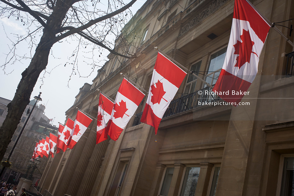 """Canadian flags hang outside Canade House in London's Trafalgar Square, Westminster. Canada House (Maison du Canada) is a Greek Revival building on Trafalgar Square in London that is part of the High Commission of Canada in London. Canada House hosts the cultural and consular sections of the High Commission. Canada House is very much a public building. It contains the High Commissioner's office, and hosts conferences, receptions, lectures, lunches and """"vernissages"""" where Canadians and Britons can meet, and has facilities for film, video and television screenings."""