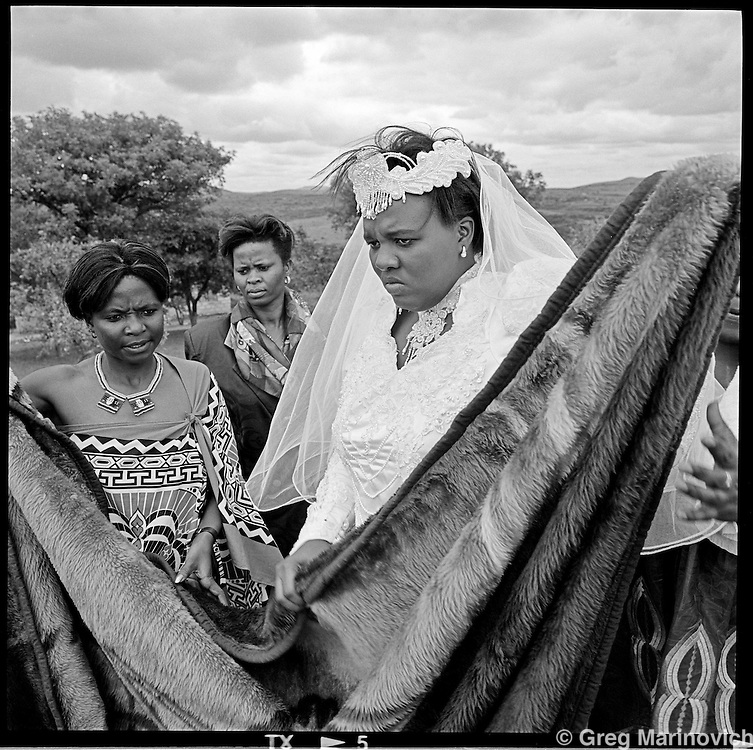 The bride and bridesmaids of groom Guava Mthembu stonily wait outside the homestead in Mkwanazi, northern KwaZulu Natal during a dispute about her attire, Nov 7, 1998. Her family are Baptists and his are staunch Nazareth Baptist Church members, and wanted her to dress in teraditonal Zulu attire - baring her breasts, which she refused to do. The issue was eventully settled with her wearing a modest sesheshwe dress. The founder Isaiah Shembe is seen as a spiritual descendent of Moses and Jesus, and th church embraces traditional Zulu values and customs. Photo Greg Marinovich
